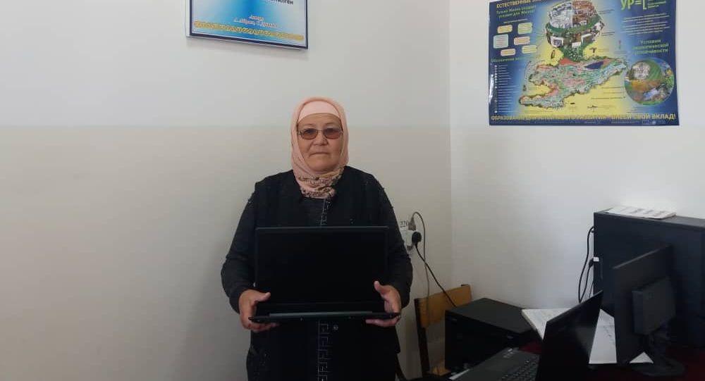 Учительница из Баткена Миргуль Эшимова, с ноутбуком купленным ей Министром образования и науки КР Каныбеком Исаковым