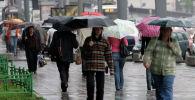 Люди идут во время сильного ливня и шквалистого ветра во время осени. Архивное фото