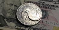 Российский рубль изображен с долларовыми купюрами и однодолларовой монетой. Архивное фото