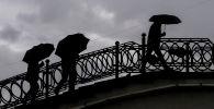 Мужчины укрываются от дождя под зонтами в Москве. 10 сентября 2020 года