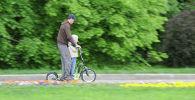 Мужчина с ребенком катаются на электрическом самокате. Архивное фото