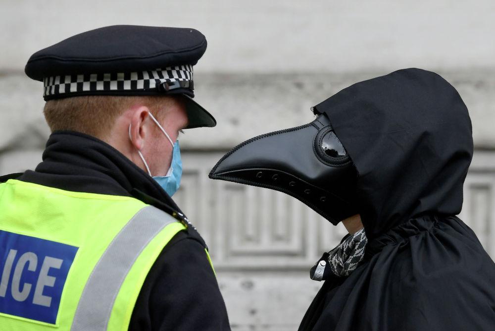 Офицер полиции разговаривает с членом группы Animal Rebellion, одетым в костюм, во время марша протеста Extinction Rebellion в Лондоне. Великобритания, 8 сентября 2020 года