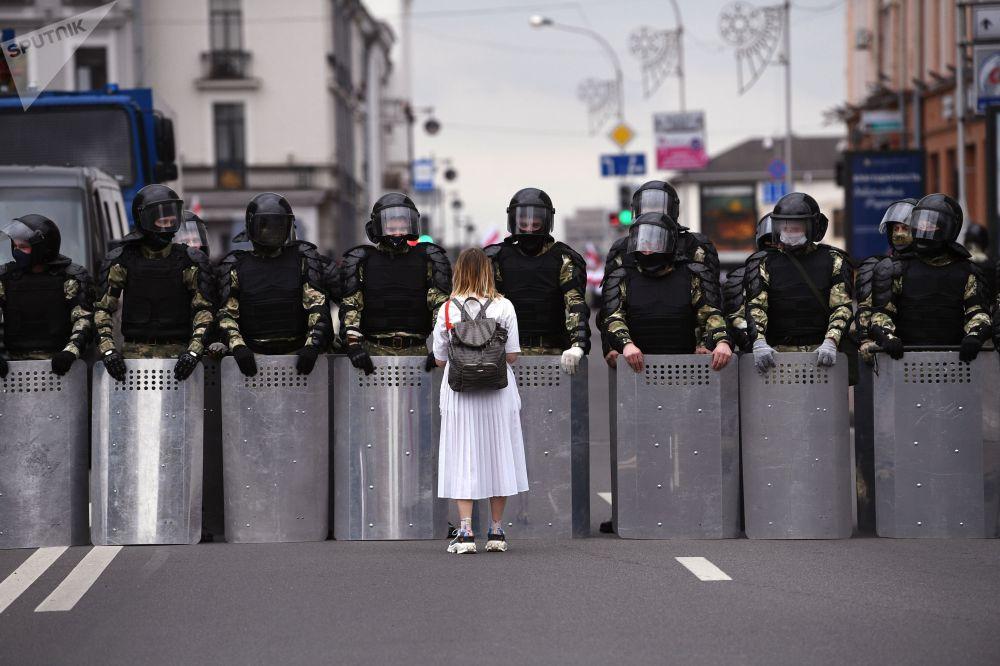 Участница несанкционированной акции оппозиции Марш единства и милиция в Минске.