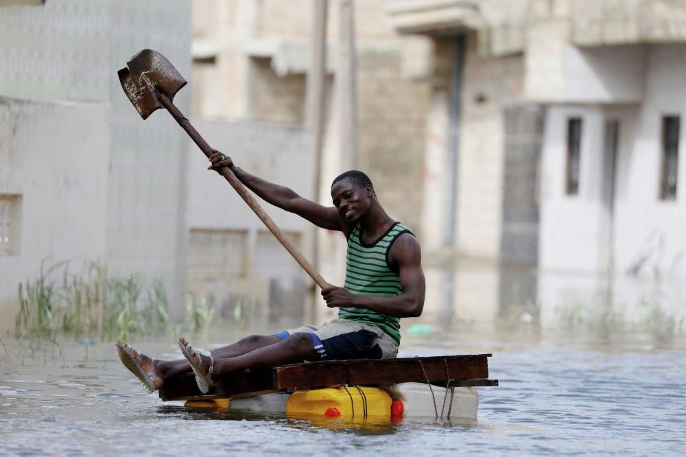 Мужчина на затопленной улице в Сенегале.
