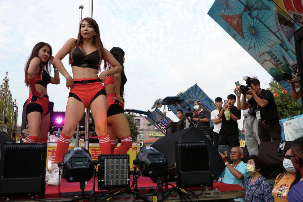 Танцоры выступают на фестивале голодных духов на Тайване.