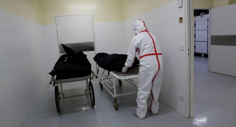Медицинский работник транспортирует тело умершего от COVID-19. Архивное фото