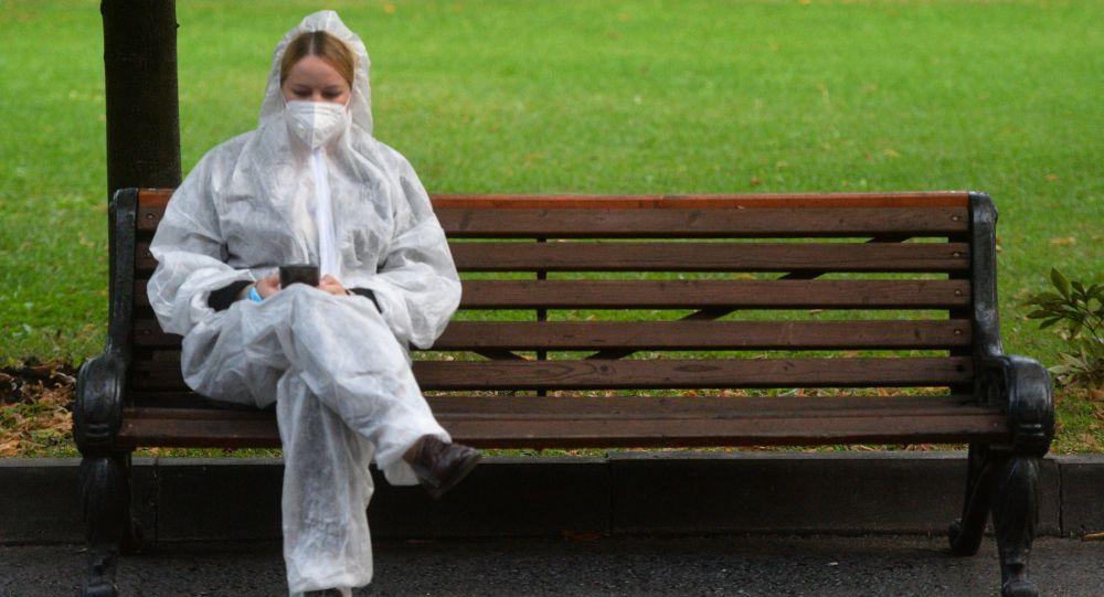 Девушка в защитном костюме сидит на скамейке в парке