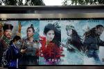 Девушка стоит у плаката рекламы фильма Мулан, на автобусной остановке в Пекине