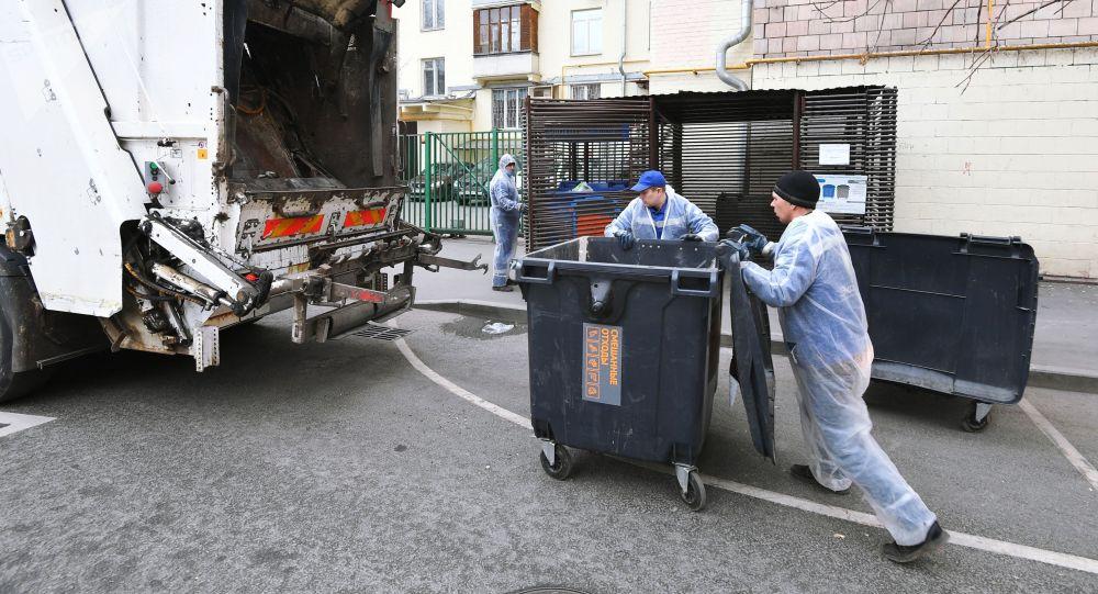Сотрудники муниципалитета выгружают содержимое мусорного контейнера в мусоровоз. Архивное фото