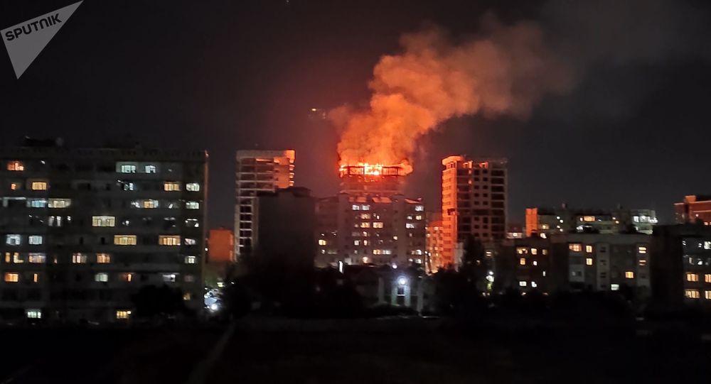 Пламя огня в строящемся многоэтажном доме по улице Тыналиева в Бишкеке. Архивное фото