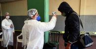 Медицинский работник измеряет температуру пассажира на автовокзале в Асунсьоне 18 мая 2020 года
