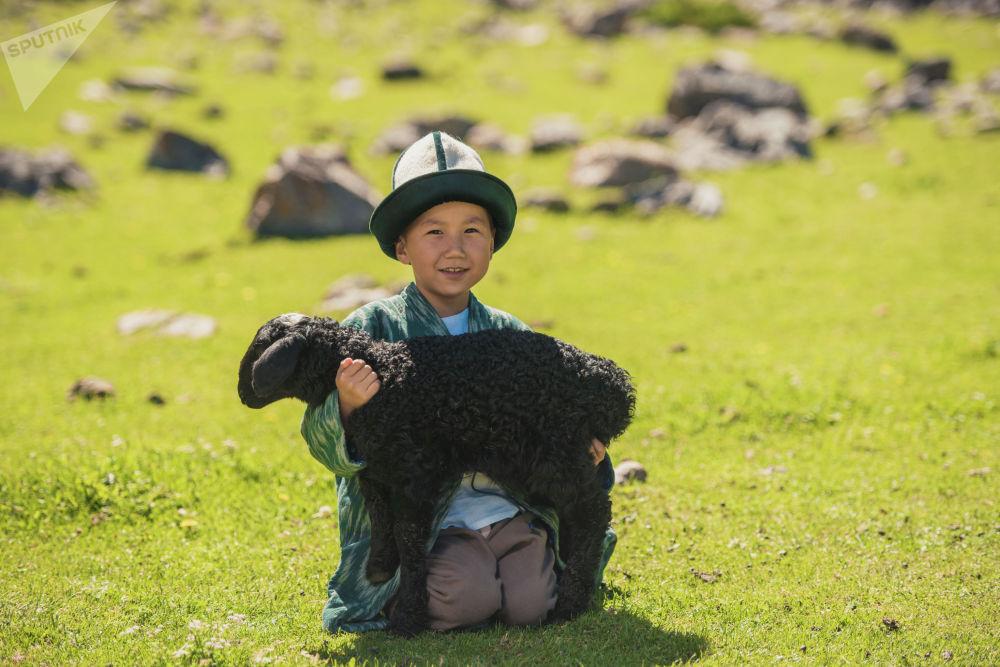 Жайлоодо козу көтөргөн бала. Анын жонундагы чапандан тарта шымына чейин кыргыздын салттуу кийимине кирет.