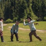 Чикит ойноп жаткан эркек балдар. Кыргыздын бул улуттук оюну жумуру таяк менен ойнолот.