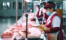 Продавец мяса на Октябрьском рынке Новосибирска. С 27 апреля в Новосибирске действует режим обязательного ношения масок в общественных местах.