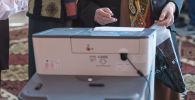 Пожилая женщина у электронной урны во время выборов в Кыргызстане. Архивное фото