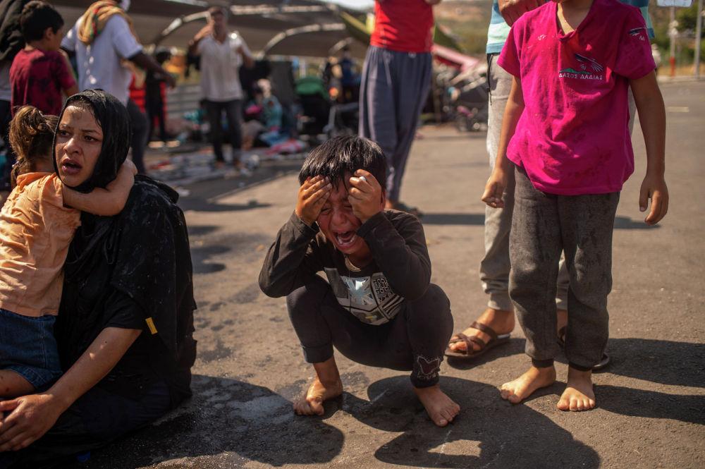 Мальчик, пострадавший от слезоточивого газа при столкновении мигрантов с полицией на греческом острове Лесбос. 12 сентября 2020 года