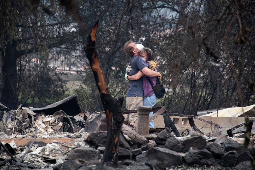 Молодые люди на месте разрушенного пожаром дома в Орегоне, США. 15 сентября 2020 года.
