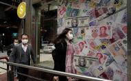 Люди проходят мимо обменного пункта, украшенного банкнотами разных стран в деловом районе Гонконга. Архивное фото