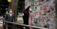 Люди проходят мимо обменного пункта, украшенного банкнотами разных стран в деловом районе Гонконга. 19 февраля 2020 года