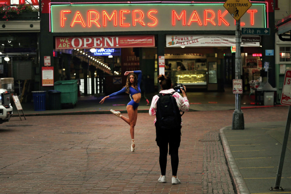 Танцовщица позирует фотографу на рынке Пайк-плейс в Сиэтле, штат Вашингтон, США, 12 сентября 2020