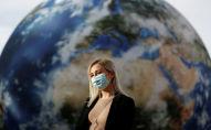 Женщина в маске стоит перед гигантской надувной моделью планеты Земля в Праге. Архивное фото