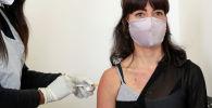 Женщина доброволец получает вакцину против COVID-19. Архивное фото