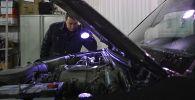 Технический эксперт проводит осмотр автомобиля на пункте технического осмотра. Архивное фото