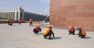 Тазалык муниципалдык ишканасынын кызматкерлери Бишкектин Ала-Тоо аянтындагы плиталарга эл түкүрүп салган сагыздарды кол менен тазалап жатышат