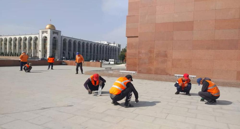 Работники муниципального предприятия Тазалык практически вручную отдирают с плит жевательные резинки на столичной площади Ала-Тоо.