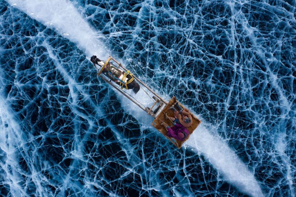 Снимок Холодная земля стал победителем в номинации Люди. Он был сделан зимой при температуре –30°C в степях Евразии. Александра Мениконци (Alessandra Meniconzi) запечатлела поездку жителей одной деревни в другую на санях по льду озера.