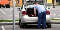 Мужчина достает вещи из багажника автомобиля. Архивное фото