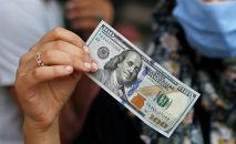 Женщина показывает стодолларовую купюру. Архивное фото
