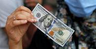 Женщина демонстрирует сто долларовую купюру. Архивное фото