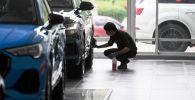 Сотрудник автосалона протирает диски автомобиля. Архивное фото