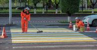 Сотрудники ремонтной службы во время нанесения разметки на дорогах Нур-Султана. Архивное фото