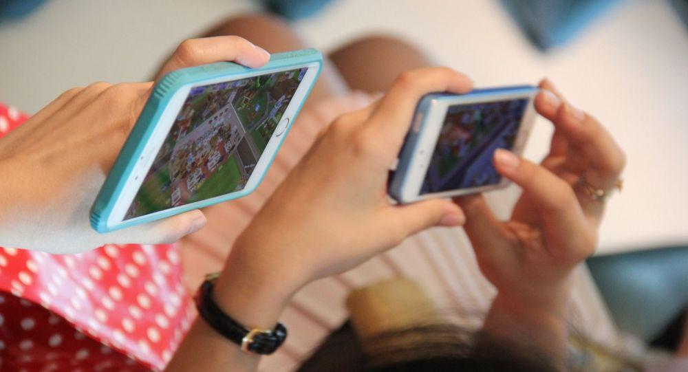 Девушки играют в игры на смартфонах. Архивное фото