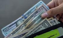 Мужчина демонстрирует кошелек с долларами США. Архивное фото