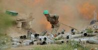 Военнослужащий Армении стреляет из артиллерийского орудия во время боя с азербайджанскими войсками в Нагорном Карабахе
