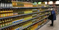 Женщина выбирает растительное масло в супермаркете. Архивное фото