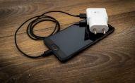 Смартфон на столе с проводом зарядки. Архивное фото