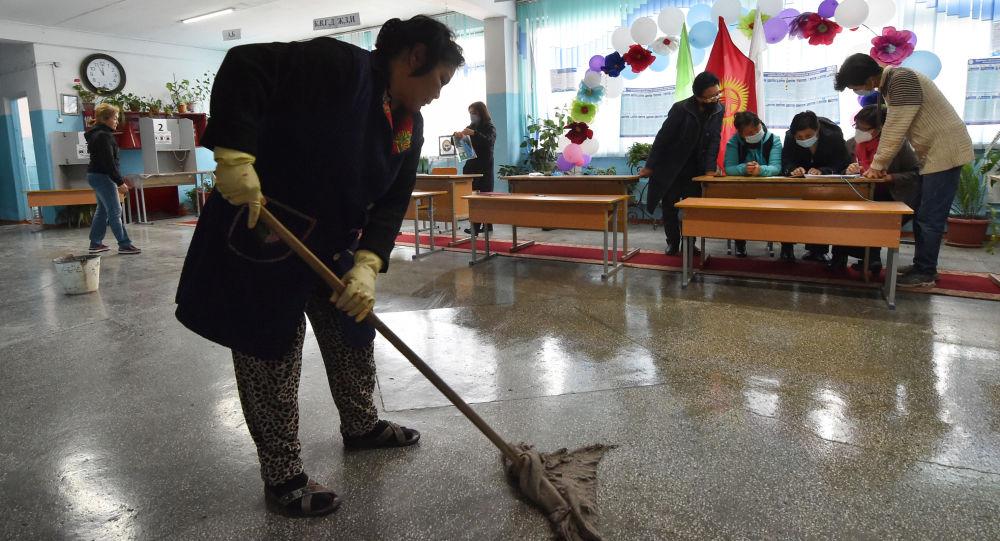 Женщина моет пол на избирательном участке. Архивное фото