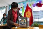 Член местной избирательной комиссии дезинфицирует переносную урну для голосования на избирательном участке