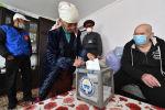 Женщина опускает бюллетень в переносную урну для голосования во время досрочного голосования накануне парламентских выборов в Кыргызстане