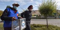 Член участковой избирательной комиссии в сопровождении сотрудника милиции ходит с переносным ящиком для голосования. Архивное фото