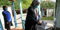 Женщина голосует дома во время досрочного голосования. Архивное фото