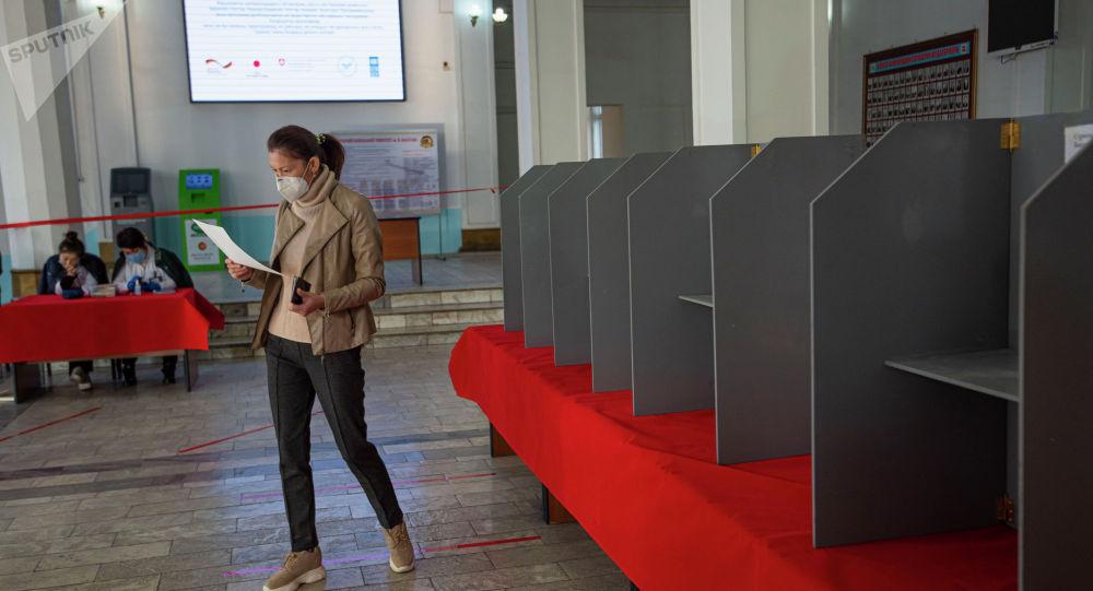 Девушка голосует на избирательном участке в Бишкеке в ходе голосования на выборах седьмого созыва ЖК