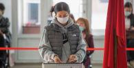 Девушка голосует на избирательном участке на выборах седьмого созыва ЖК. Архивное фото