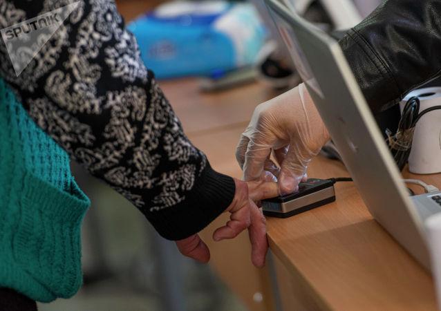 Прохождение биометрической идентификации на избирательном участке №1327 в Бишкеке в ходе голосования на выборах седьмого созыва ЖК