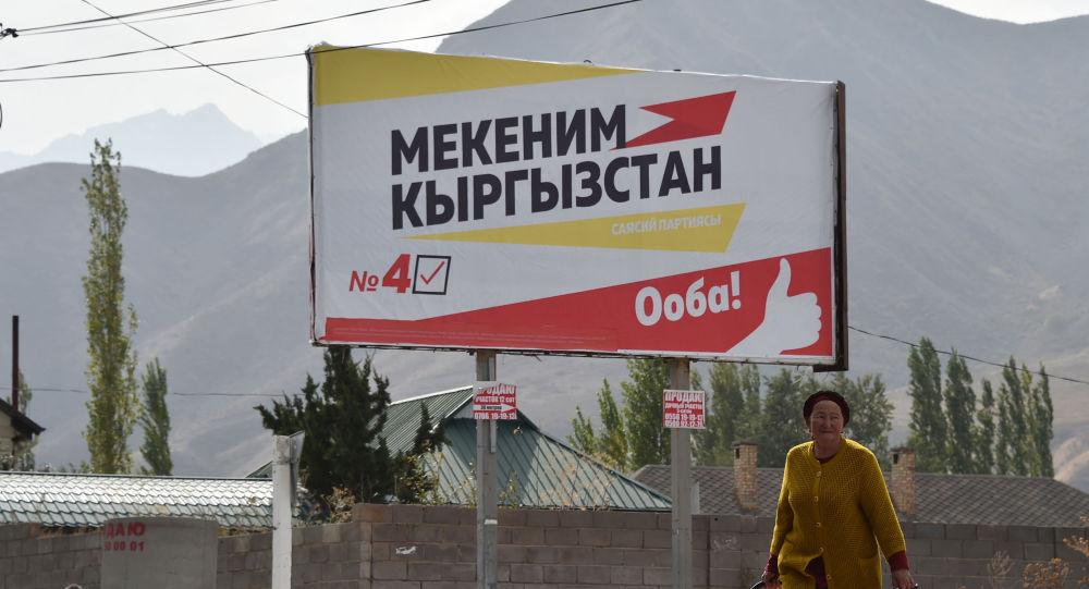 Женщина проходит мимо агитационного баннера партии Мекеним Кыргызстан. Архивное фото