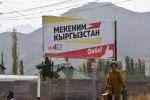 Женщина проходит мимо агитационного баннера партии Мекеним Кыргызстан в селе Кой-Таш. Архивное фото